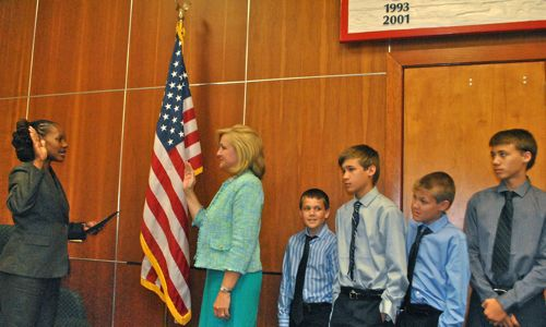 New Commissioner Shelly Petrolia takes the oath while her four sons look on.